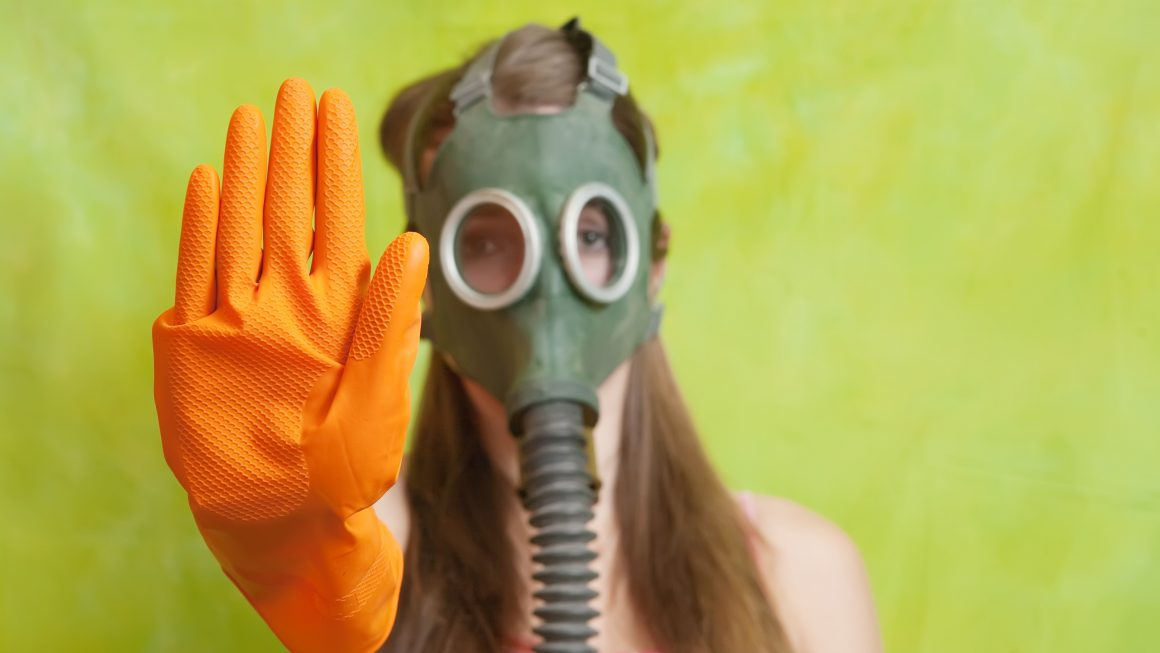 girl in gas mask pointing STOP, Focus on glove